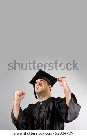 A recent graduate posing in his cap and gown and celebrating.  Isolated over a silver background with copy space. - stock photo