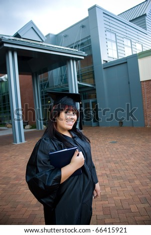 A recent graduate posing outdoors with her diploma tucked in her arm. - stock photo