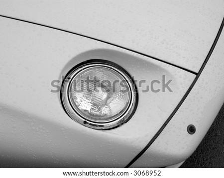 A recessed headlight on a Porsche 928 just after a rain shower. - stock photo