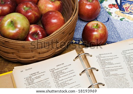 A recipe book turned to apple pie recipe - basket of apples. - stock photo