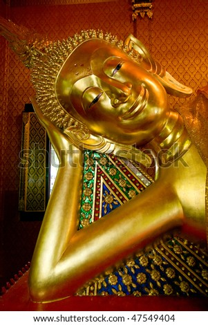 A reclining buddha in a buddhist temple. - stock photo