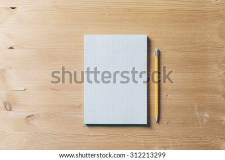 A recycled paper notebook checked with a black pencil with the eraser at the top, are arranged on a brown wooden table. View from the top - stock photo