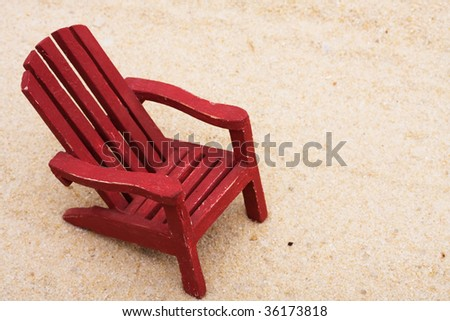 A red Adirondack chair sitting in the sand on the beach, summer vacation