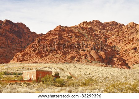A red adobe and stucco home in the desert with red rock hills in background - stock photo
