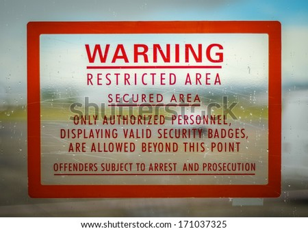 A Red Airport Security Restricted Area Warning Sign - stock photo