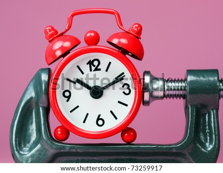 A red alarm clock placed in a Grey clamp against a pastel pink background, asking the question do you manage your time effectively? - stock photo