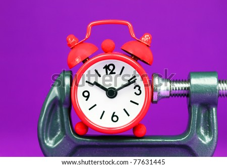A red alarm clock placed in a Grey clamp against a pastel purple background, asking the question do you manage your time effectively. - stock photo