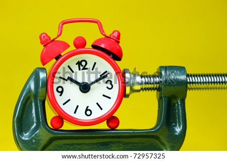 A red alarm clock placed in a Grey clamp against a pastel yellow background, asking the question do you manage your time effectively? - stock photo