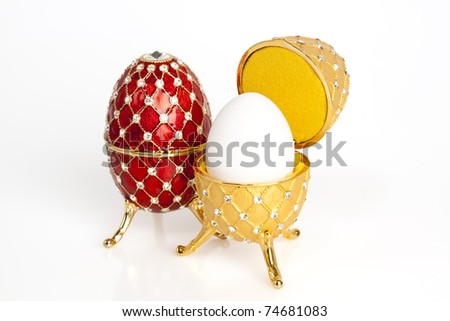 A red and a yellow jewel Easter egg with a real egg inside the yellow one