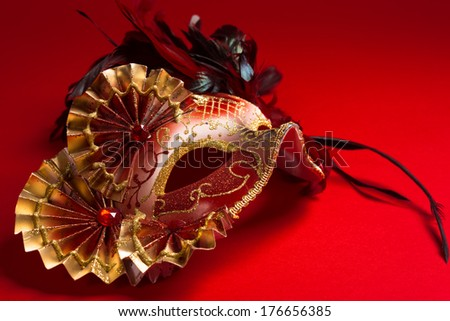 A red and gold venetian, mardi gras mask on a red bakground - stock photo