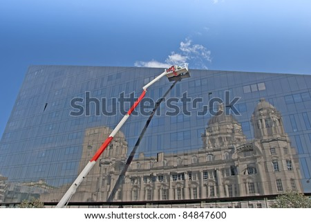 A Red and White Cherry Picker and Glass Building with Reflection of Historic Building - stock photo
