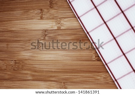 A Red and White Kitchen Towel Laying on a Bamboo Cutting Board or Counter in Vintage Tones with Room for your text or words.  Horizontal or Vertical. - stock photo
