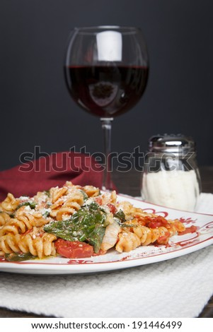 A red and white plate filled with Fusilli pasta, prepared with fresh baby spinach, diced tomatoes and parmesan cheese; a glass of red wine and shaker of parmesan cheese sit off to the side - stock photo
