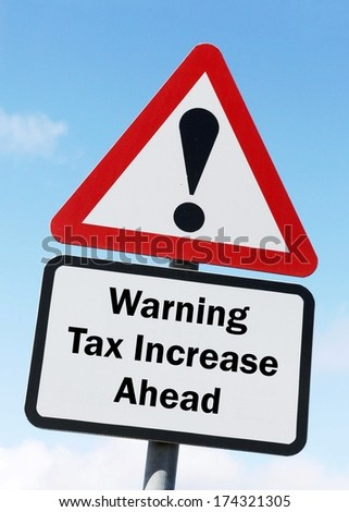 A red and white road sign depicting a warning about an increase in taxes ahead. - stock photo