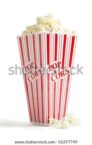 A red and white striped theater type popcorn box filled over the top. - stock photo