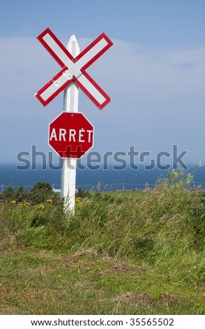 a red and white train crossing stop sign written in french