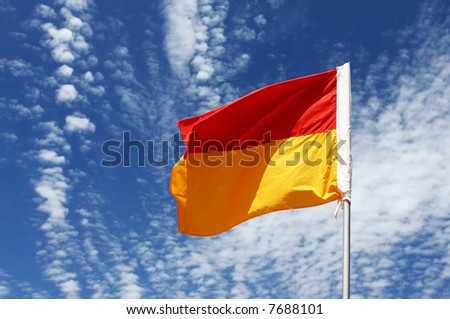 A red and yellow swimming safety flag on an Australian beach, against vibrant blue sky with scattered cloud.  Swim between the flags! - stock photo