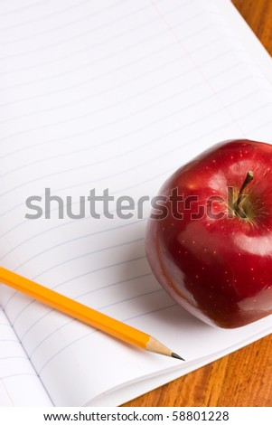 A red apple and pencil sitting on an opened notebook.  Concept of education.
