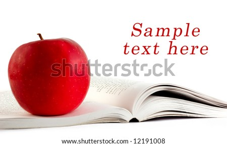 A red apple on a book and copy space for sample text here - stock photo