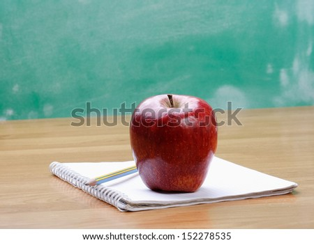 A red apple on a notebook - stock photo