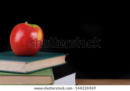 A red apple on top of three old hardcover books with a blackboard background and copy space.