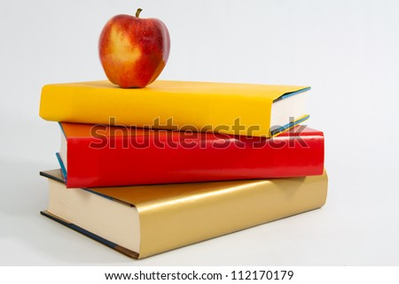 A red apple sits atop a stack of three books. - stock photo