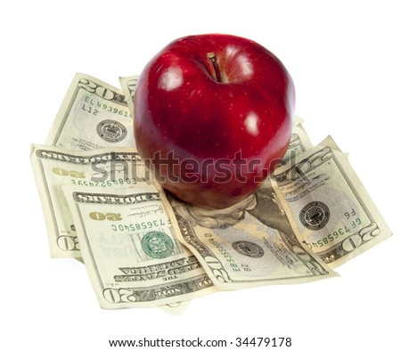 A red apple sits on top of a pile of $20 bills to illustrate the cost of education, food, or health care.  Studio shot on a white background. - stock photo