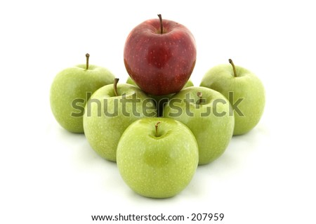 A red apple sits on top of six green apples - stock photo
