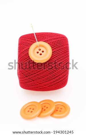 A red ball of thread or string with a button and needle on the string. - stock photo