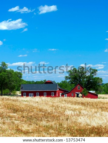 A red barn and farmhouse sit amid golden fields of wheat and grass