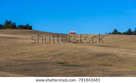 A Red Barn On A Hill Top