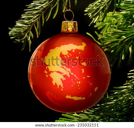 A red bauble with the golden shape of  Greece hanging on a christmas tree isolated on black.(series) - stock photo