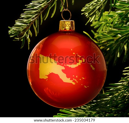 A red bauble with the golden shape of  Papua New Guinea hanging on a christmas tree isolated on black.(series) - stock photo