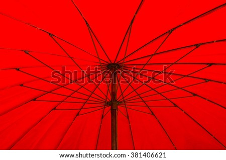 A red beach umbrella blocks out the hot, tropical sun. - stock photo
