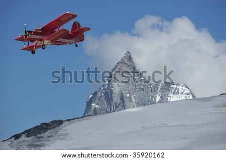 a red bi-plane flies close to the Matterhorn - stock photo