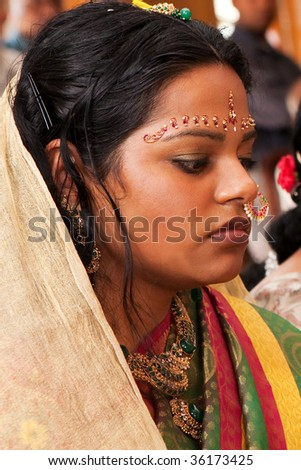 A Red Bindi is applied to a Hindu bride's forehead - stock photo