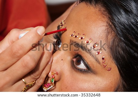A Red Bindi is applied to a Hindu brides forehead - stock photo