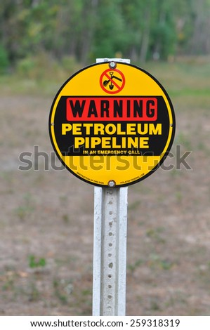 A red, black and yellow sign on a post reading Warning Petrolium Pipeline against a natural background - stock photo