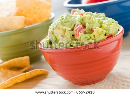 A red bowl filled with guacamole, a green bowl filled with chips and a blue bowl in the background. - stock photo
