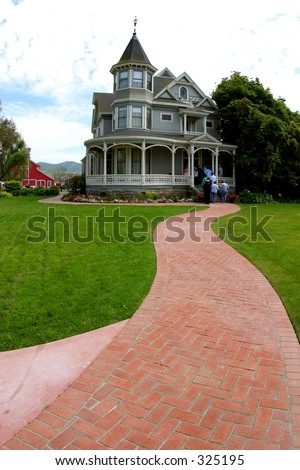 A red-brick walkway leads to a Victorian farm house in Southern California. - stock photo