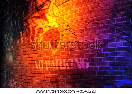 "A red brick wall dramatically lit by a bright yellow light.  A ""No Parking"" sign and graffiti  cover the wall. - stock photo"