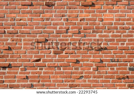 A red brick wall with some broken or protruding bricks.