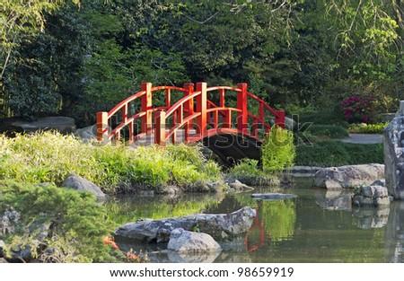 a red bridge in a japanese garden