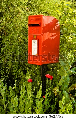 A red British letterbox in a rural setting. - stock photo