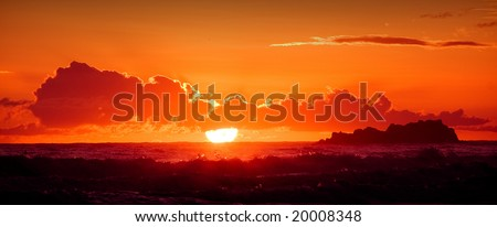 A red burning sunset with the silhouett of an island over a stormy ocean - stock photo
