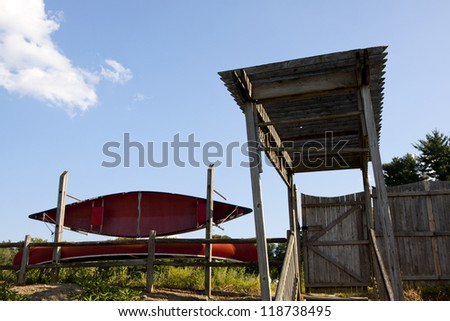 A red canoe next to the entrance stairway to a lake.