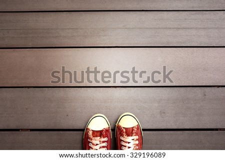 a red canvas shoes on the wood ground - stock photo