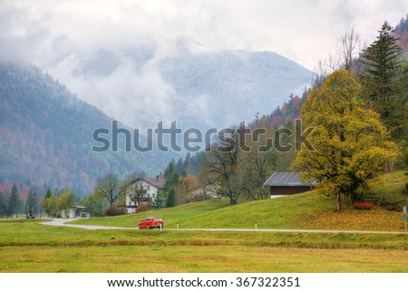 A red car traveling on a country road between green fields, mountains and autumn forest to a farmhouse at beautiful hillside ~ Scenery of romantic fall countryside in  Bavaria Germany - stock photo