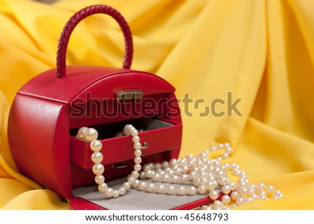 A red case with jewels is on the yellow background - stock photo