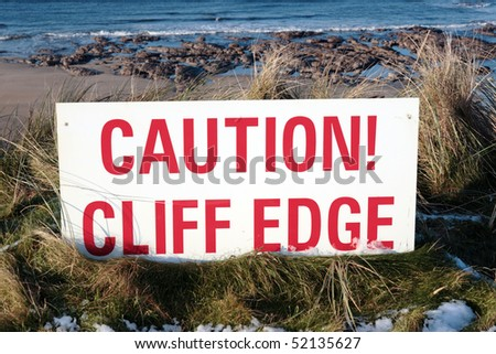 a red caution sign on a cliff edge in snow covered ballybunion - stock photo